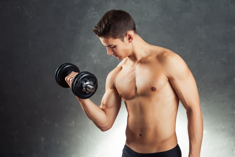 Bodybuildermann, der mit Dummkopf trainiert lizenzfreie stockfotografie