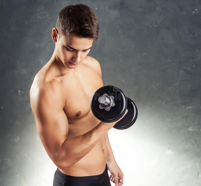 Bodybuildermann, der mit Dummkopf trainiert lizenzfreies stockbild