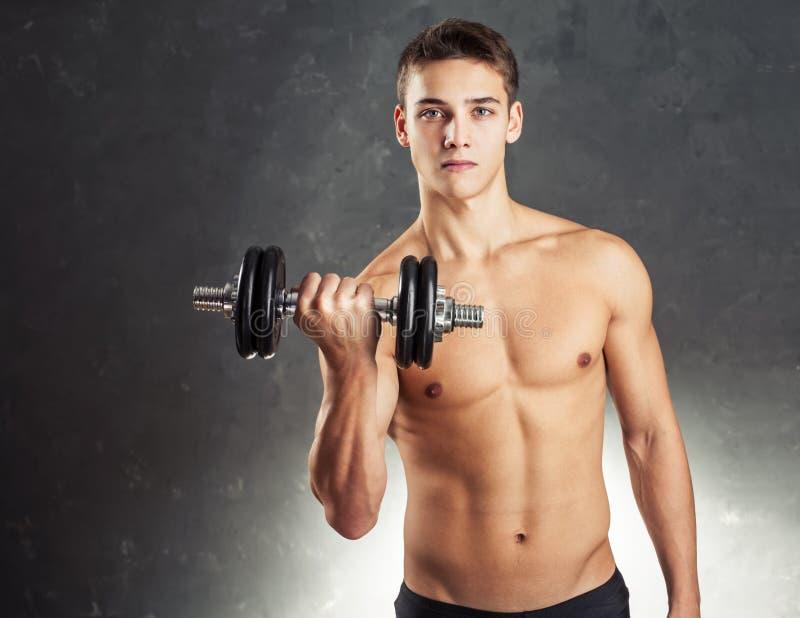 Bodybuildermann, der mit Dummkopf trainiert stockfotos