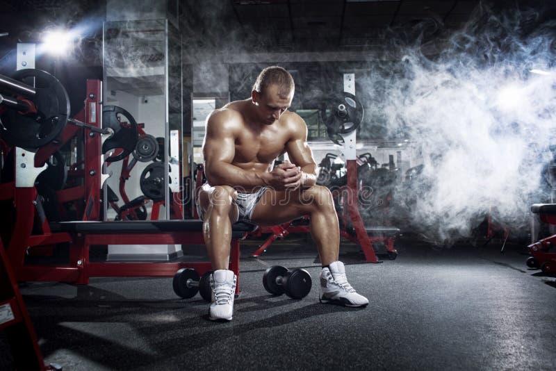 Bodybuildermann, der nach Training in der Turnhalle sich entspannt stockbild
