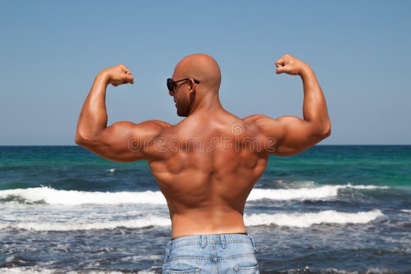 Bodybuildermens met naakte borst in jeans stock foto's