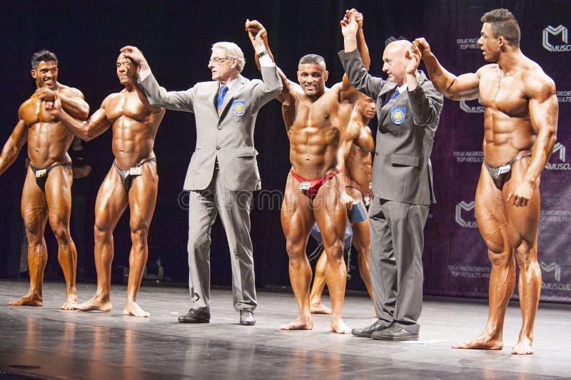 Bodybuilders świętują ich zwycięstwo na scenie z urzędnikami fotografia royalty free