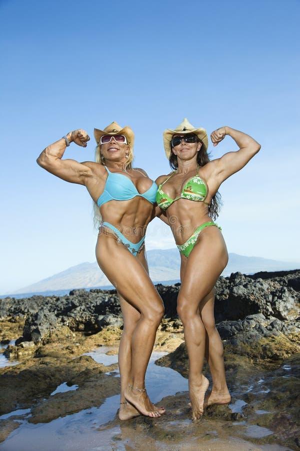 Bodybuilders delle donne alla spiaggia. immagine stock