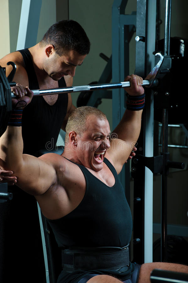 Bodybuilders training in gym. Two strong muscular mans training body in gym stock photo