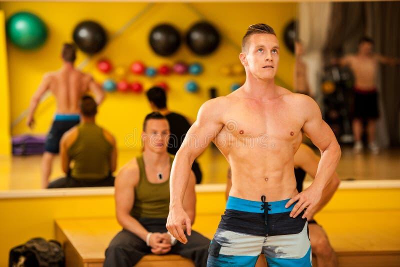 Bodybuildertrein het stellen vóór de concurrentie stock fotografie