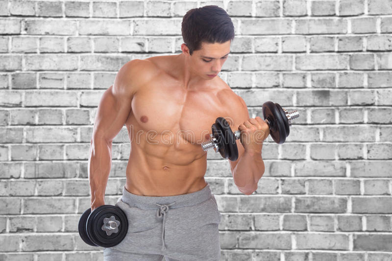 Bodybuilding bodybuilder muscles biceps body builder building wa. Bodybuilding bodybuilder muscles biceps body builder building brick wall dumbbell training royalty free stock photography