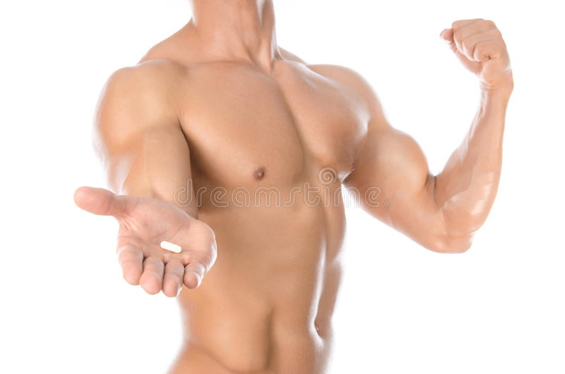 Bodybuilding and chemical additives: handsome strong bodybuilder holding colored pills isolated on white background in studio stock photo