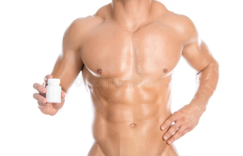 Bodybuilding and chemical additives: handsome strong bodybuilder holding a white jar of pills on white isolated background in stud stock photo