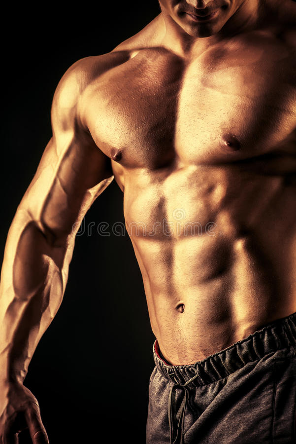 Bodybuilding. Close-up shot of a handsome muscular bodybuilder posing over black background stock photography