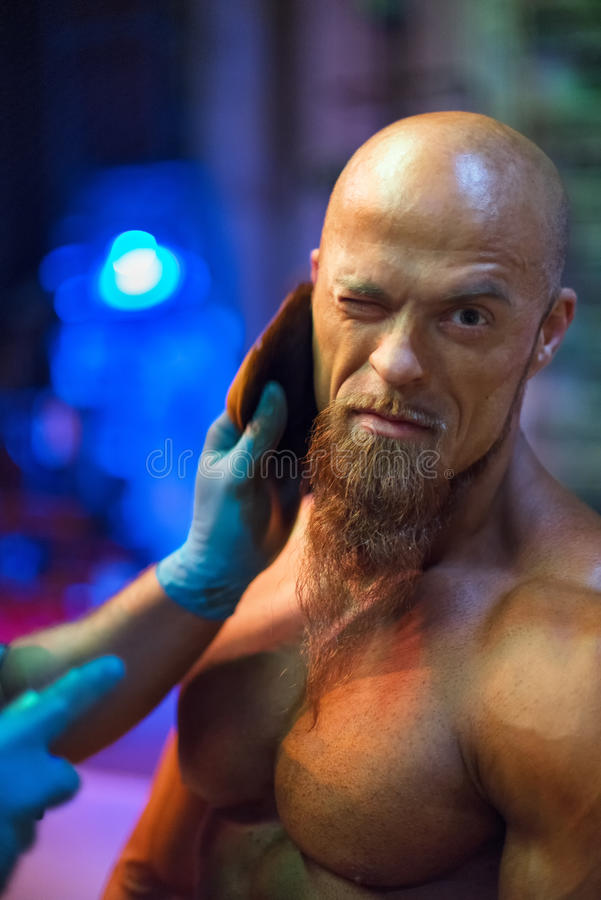 Bodybuilding competition backstage: contestant being oiled and fake tan applied to skin. Selective focus royalty free stock photo