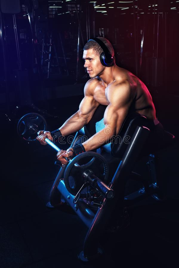 Bodybuilder doing exercises with barbell in gym stock photography