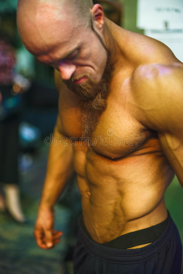 Bodybuilding contest behind the scenes: the contestant is preparing for the performance. Selective focus stock photography