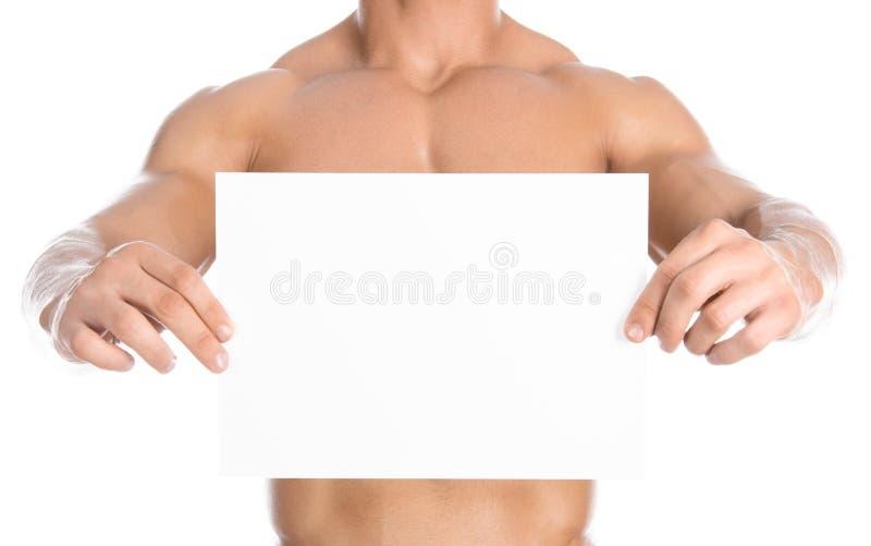 Bodybuilding en reclame: een aardige sterke bodybuilder die een document witte lege die kaart houden op witte achtergrond in stud royalty-vrije stock foto's