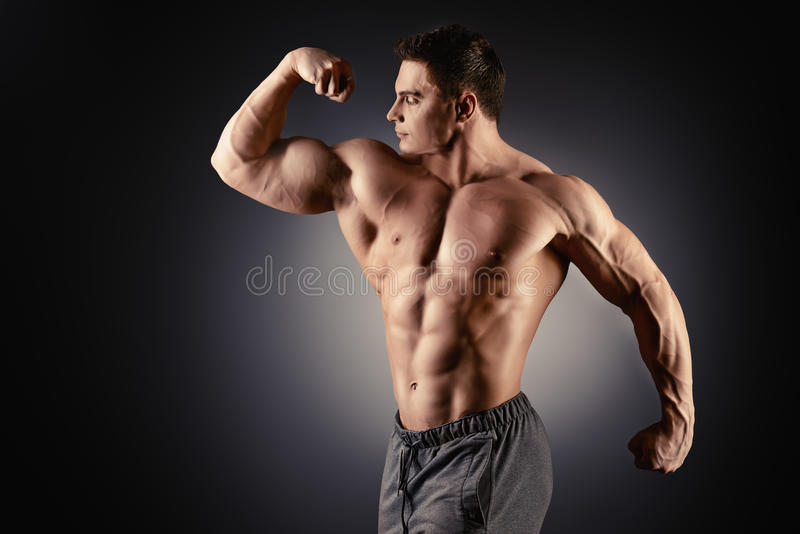 Bodybuilding. Handsome muscular bodybuilder posing over black background stock images
