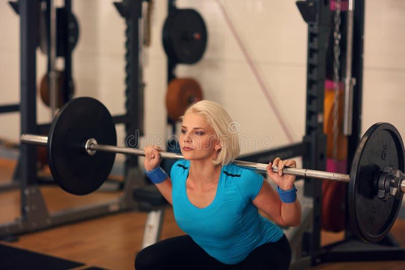bodybuilding Mujer fuerte del ajuste que ejercita con el barbell muchacha que hace posiciones en cuclillas con los pesos grandes fotos de archivo libres de regalías