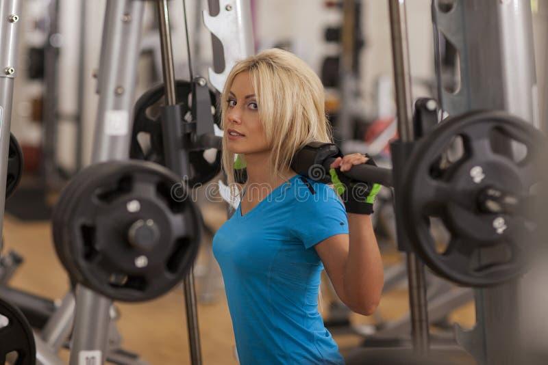 bodybuilding Mujer fuerte del ajuste que ejercita con el barbell pesos de elevación de la muchacha en gimnasio imagen de archivo