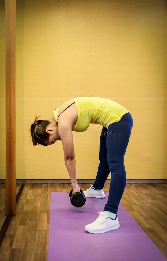 bodybuilding Mujer fuerte del ajuste que ejercita con pesas de gimnasia fotografía de archivo