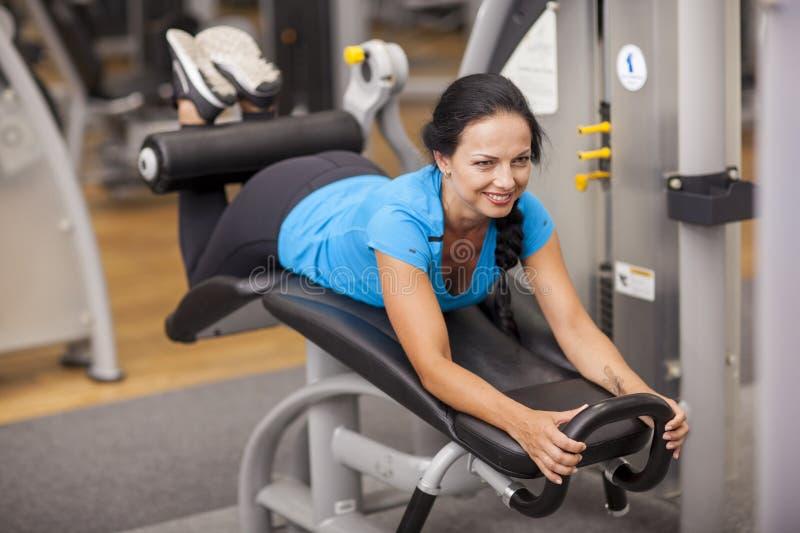 bodybuilding mujer que ejercita en gimnasio con la ejercicio-máquina imágenes de archivo libres de regalías