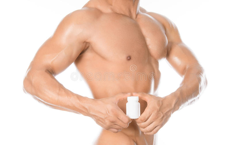 Bodybuilding- och kemikalietillsatser: den stiliga starka kroppsbyggaren som rymmer en vit krus av preventivpillerar på vit, isol arkivfoton