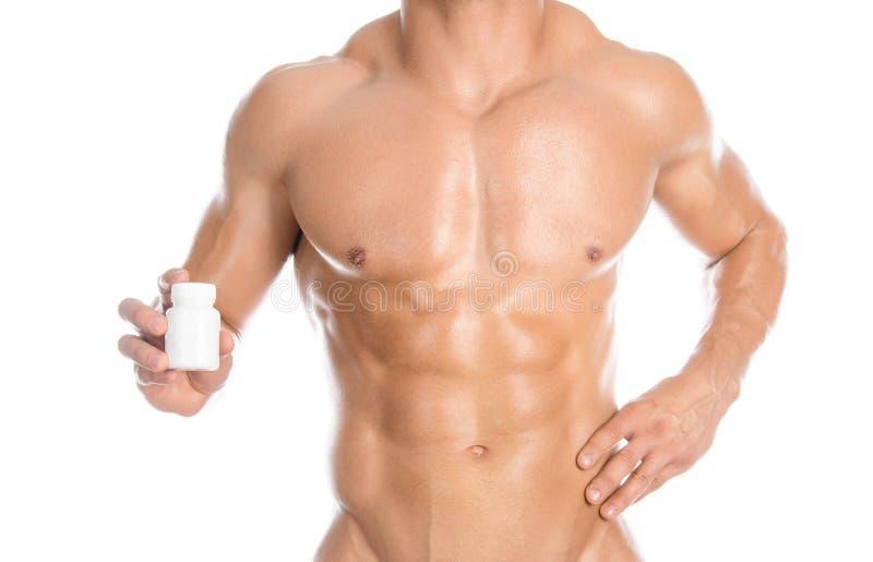 Bodybuilding- och kemikalietillsatser: den stiliga starka kroppsbyggaren som rymmer en vit krus av preventivpillerar på vit, isol arkivfoto