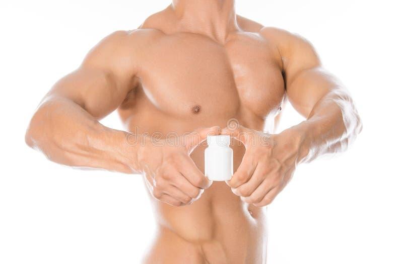 Bodybuilding- och kemikalietillsatser: den stiliga starka kroppsbyggaren som rymmer en vit krus av preventivpillerar på vit, isol royaltyfri bild