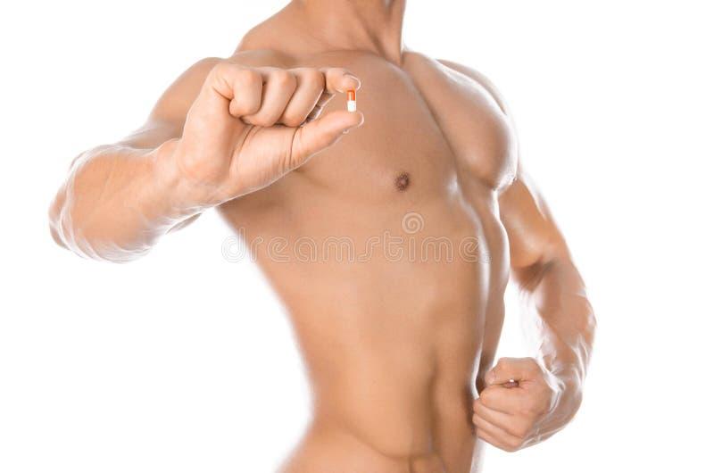 Bodybuilding- och kemikalietillsatser: det stiliga starka kroppsbyggareinnehavet färgade preventivpillerar som isolerades på vit  arkivbild
