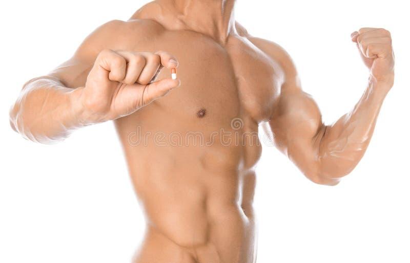 Bodybuilding- och kemikalietillsatser: det stiliga starka kroppsbyggareinnehavet färgade preventivpillerar som isolerades på vit  royaltyfri bild