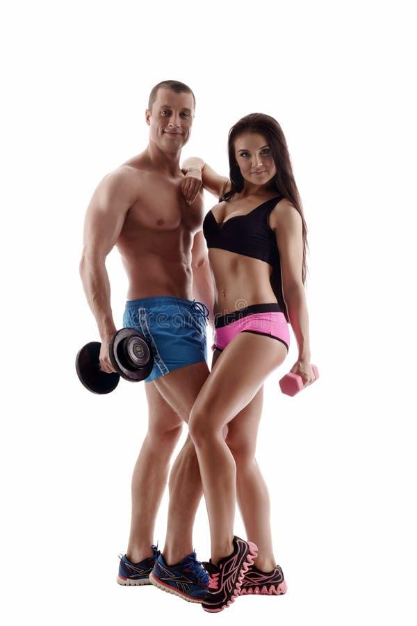 bodybuilding Pares deportivos que presentan con pesas de gimnasia fotografía de archivo libre de regalías