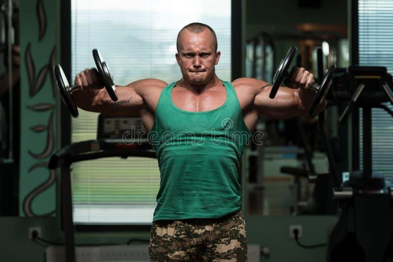 Bodybuilding-Schulter-Übung mit Dummköpfen lizenzfreie stockfotos
