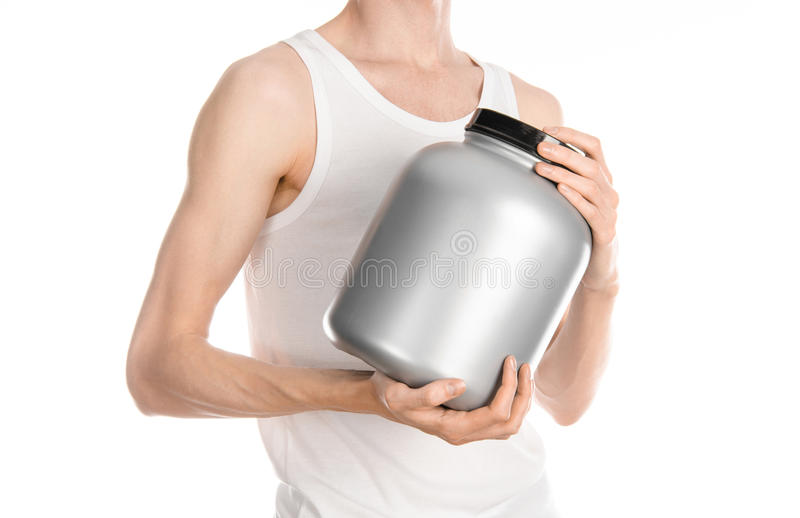 Bodybuilding and Sports theme: a thin man in a white T-shirt and jeans holding a plastic jar with a protein isolated on a white ba stock photography