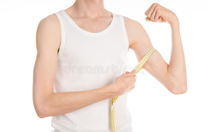 Bodybuilding and Sports theme: a thin man in a white T-shirt and jeans with measuring tape isolated on a white background in studi stock photography