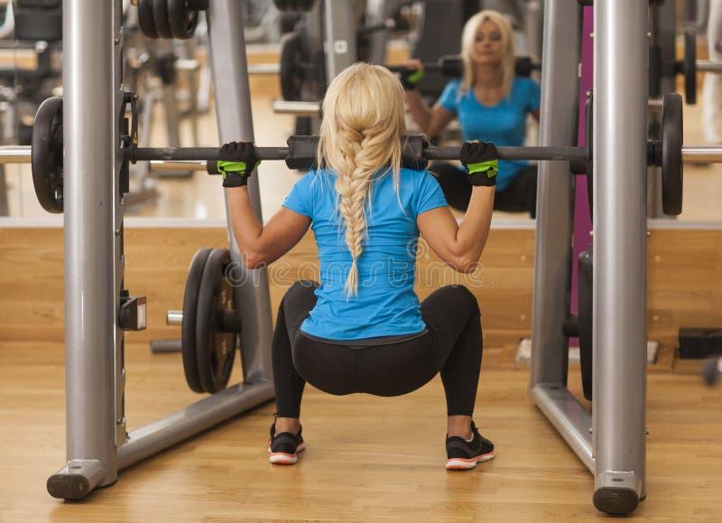 bodybuilding Starke Sitzfrau, die mit Barbell trainiert anhebende Gewichte des Mädchens in der Turnhalle stockbild