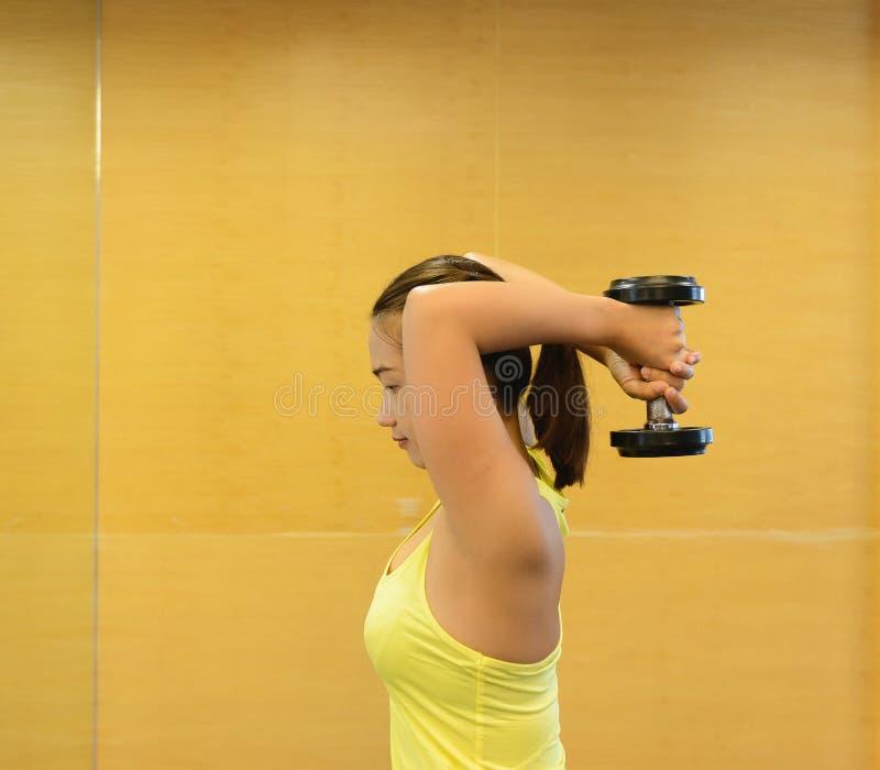 bodybuilding Starke Sitzfrau, die mit Dummköpfen trainiert lizenzfreie stockbilder