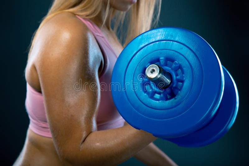 bodybuilding Starke Sitzfrau, die mit Dummköpfen trainiert Anhebende Gewichtsatelieraufnahme des muskulösen blonden Mädchens auf  lizenzfreie stockbilder