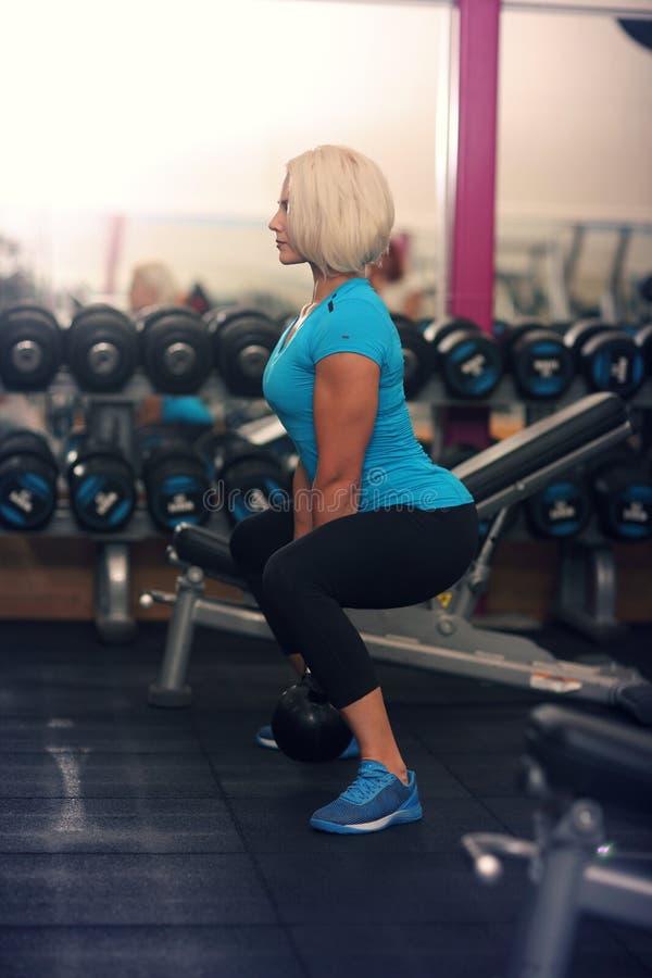 bodybuilding Sterk geschikt wijfje die met gewicht uitoefenen blonde meisje het opheffen gewichten in gymnastiek Sterke Vrouw royalty-vrije stock fotografie