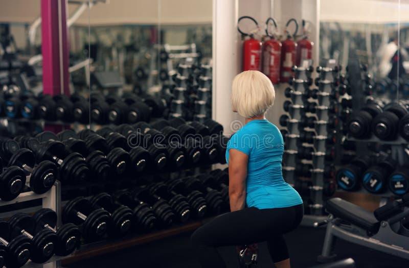 bodybuilding Sterk geschikt wijfje die met gewicht uitoefenen blonde meisje het opheffen gewichten in gymnastiek Sterke Vrouw stock fotografie