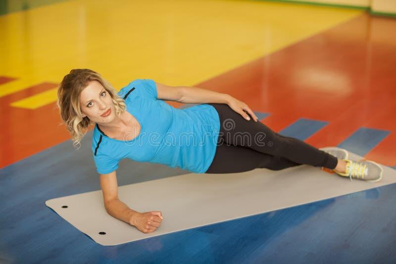 bodybuilding vrouw die op mat in geschiktheidsklasse uitoefenen Vrouwelijke training in gymnastiek die plank doen stock afbeelding