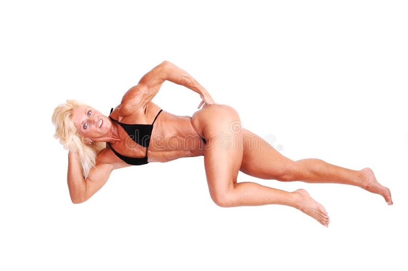 Bodybuilding woman. A blond muscular bodybuilding girl lying on the floor in the studio shooing her strong legs and the upper body and arms, over white stock photo