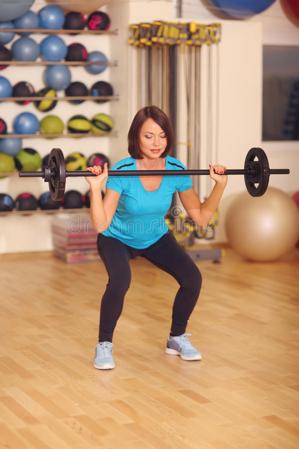 Bodybuilding. woman exercising with barbell in fitness class. Female workout in gym doing squats with weight. Bodybuilding. woman exercising with barbell in stock photography