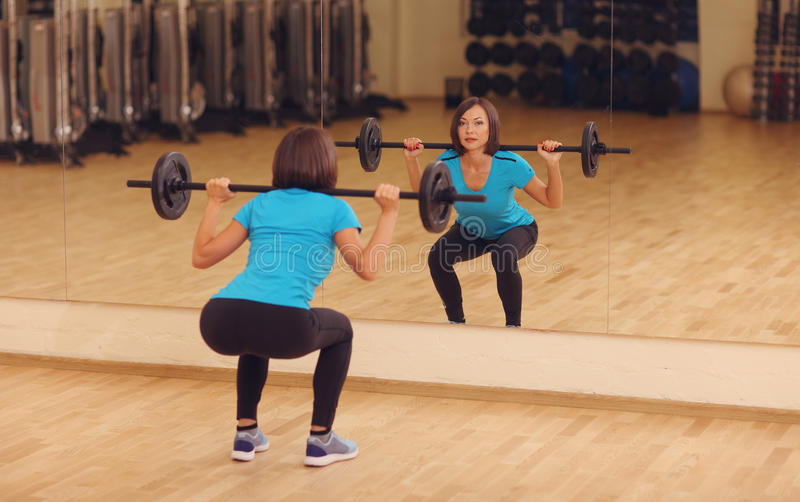 Bodybuilding. woman exercising with barbell in fitness class. Female workout in gym doing squats with weight. Near mirror stock photos