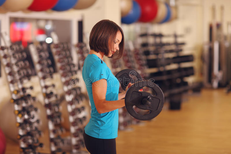 Bodybuilding. woman exercising with barbell. girl lifting weights in gym. Bodybuilding. woman exercising with barbell and looking on it. girl lifting weights in royalty free stock image