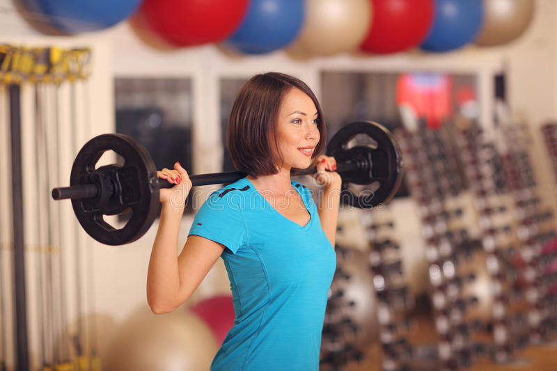 Bodybuilding. woman exercising with barbell in fitness class. Female workout in gym with barbell. Bodybuilding. woman exercising with barbell on shoulders in royalty free stock image