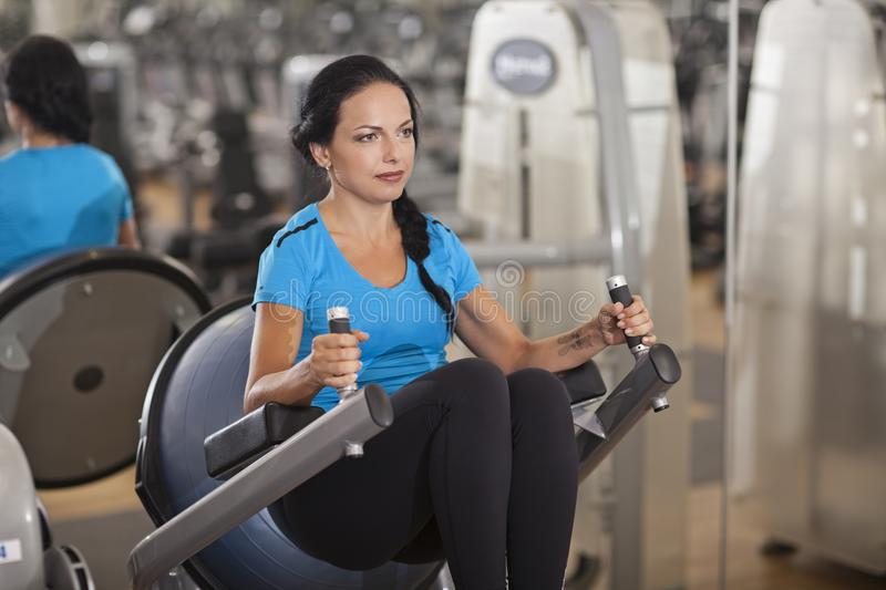 Bodybuilding. woman exercising in gym with exercise-machine. Bodybuilding. woman exercising in gym abs press legs up stock images
