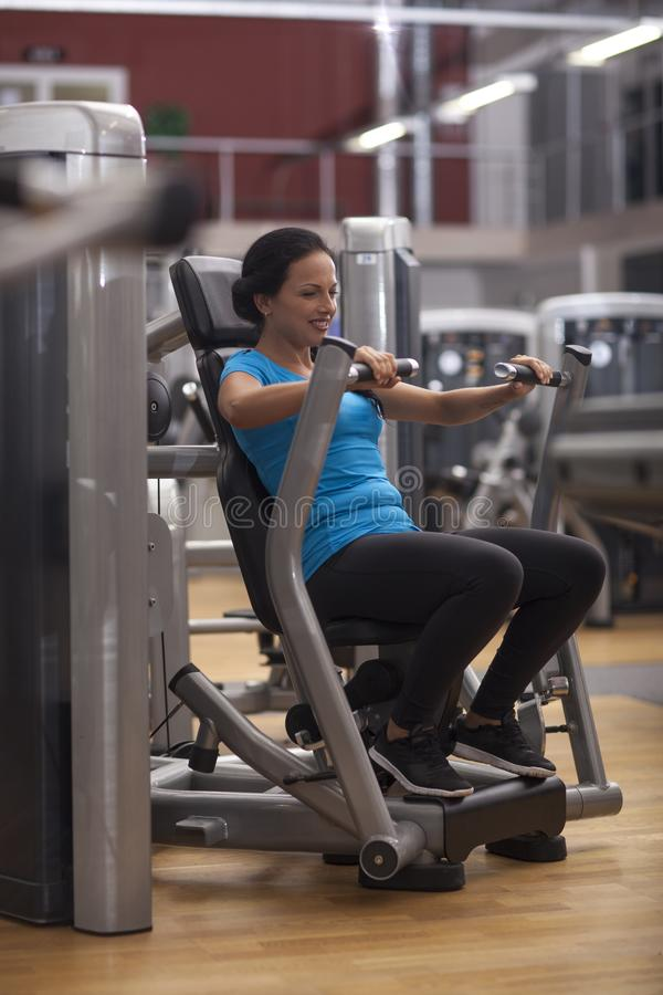 Bodybuilding. woman exercising in gym with exercise-machine arms back and shoulders. Bodybuilding. woman exercising in gym - arms back and shoulders royalty free stock photos