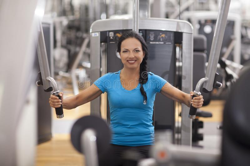 Bodybuilding. woman exercising in gym with exercise-machine. Bodybuilding. woman exercising in gym with exercise-machine royalty free stock photography