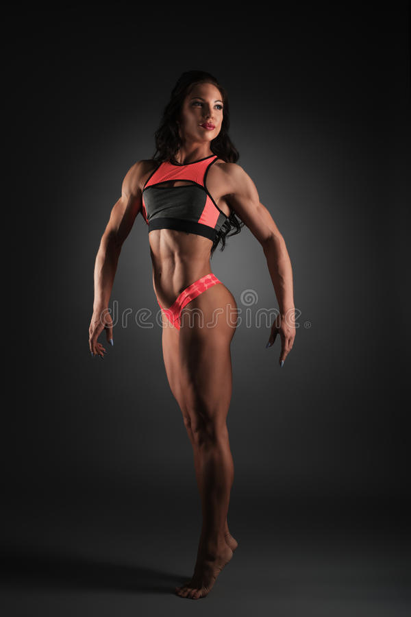 Bodybuilding. Woman posing showing her muscles royalty free stock photography