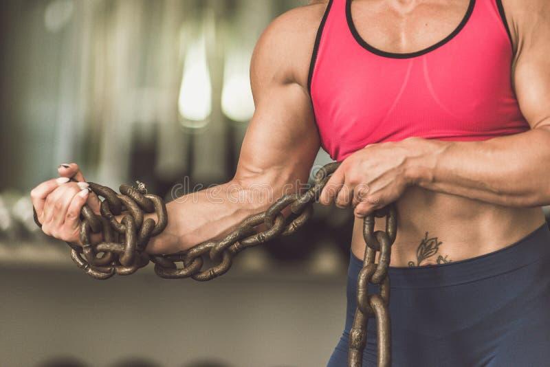 Bodybuildingflickan är i idrottshallen med en kedja i henne händer royaltyfria foton