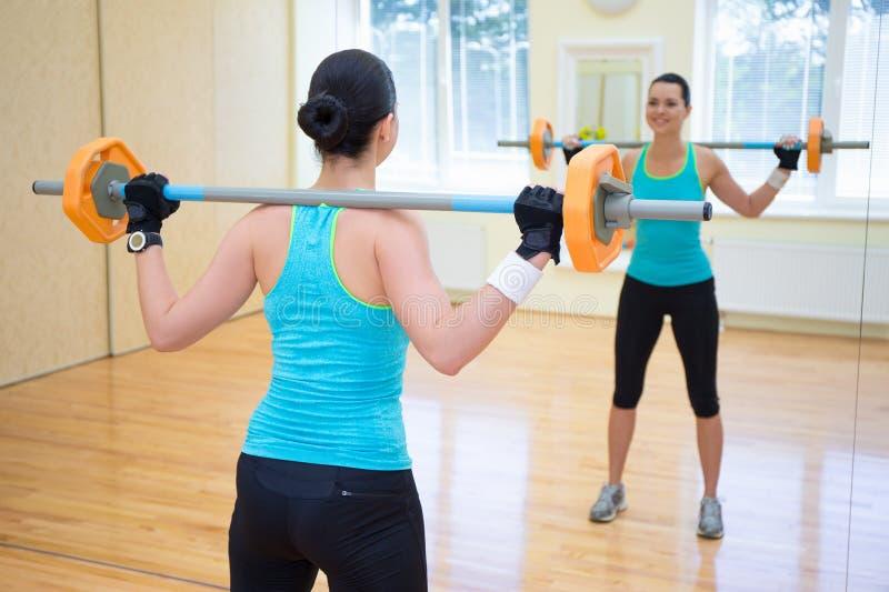 Bodybuildingsconcept - achtermening van het jonge vrouw uitoefenen met stock fotografie