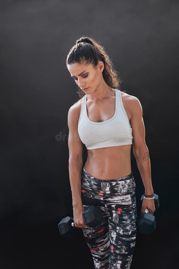 Bodybuildingsmodel die met zware domoren uitoefenen stock afbeelding