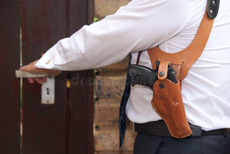 Bodyguard with gun. Opens the door stock images